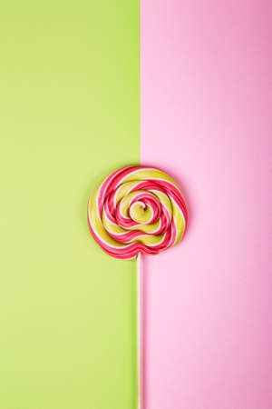 Twisted round pink and green colorful lollipop candy placed on pink and green background. Flat lay concept.
