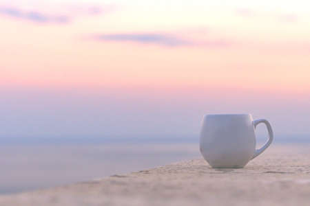 White cup of coffee placed on the terrace outside next to morning sky. Imagens