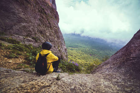 Woman in sport helmet sits at the edge of a rock and looks at the view of nature infron of her. Travel and landsacpe.