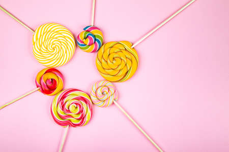 Many colorful lollipop candys arranged in heap with heart shaped candy in the center on pink background. Flat lay concept.