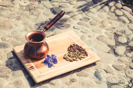 Composition of coffee turka and cardamom grains in heart shape and violet flower on stone background. Flat lay style. Imagens