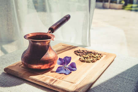 Composition of coffee turka and cardamom grains in heart shape and violet flower on wooden board next to window. Imagens
