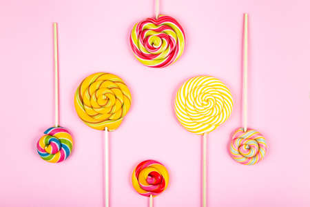 Group of colorful lollipop twisted candys placed  on pink background. Flat lay concept.