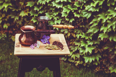 Two bronze colored coffee turka with violet flowers, cardamom and coffee grains on wooden board served outside in the garden.