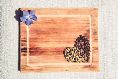 Composition of coffee and cardamom grains in heart shape and violet flower on wooden board. Flat lay style.