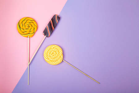 Twisted round and ice cream colorful lollipop candys placed on pink and violet background. Flat lay concept. Imagens