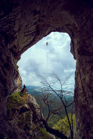 Woman rappeling using special equipment in the opened cave looking at the view of forest, sky and clouds. Mountaineering style abseil.