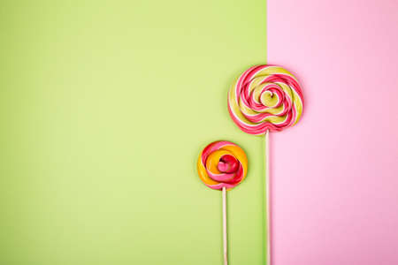 Two twisted round pink and green colorful lollipop candy placed on pink and green background. Flat lay concept. Imagens