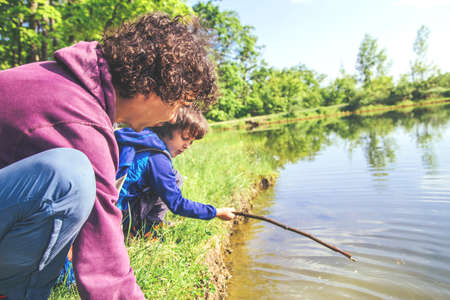 Father plays with his son outdoor near the pond, they play fishing together.