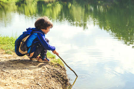 Little kid play with stick looks like rod and fishing on the lake in the forest on a sunny day. Imagens