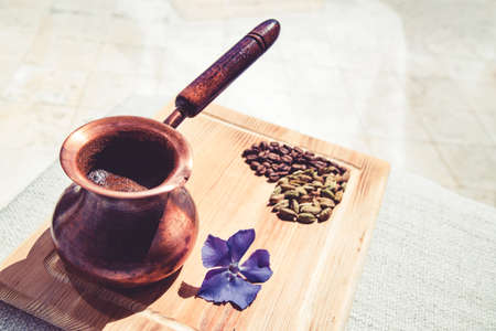 Composition of coffee turka and cardamom grains in heart shape and violet flower on wooden board next to window. Flat lay style.