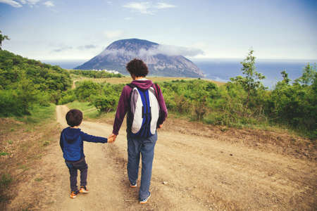 Father and son walking on the road together holding by the hands opposite green hill, mountain and sea. Back view. Imagens