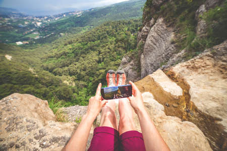 Woman makes photo of her boots and landscape background sitting at the edge of a rock near stream. View on behalf of photographer. Standard-Bild