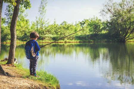 Niño pequeño juega con palo parece caña y pesca en el lago en el bosque en un día soleado. Foto de archivo