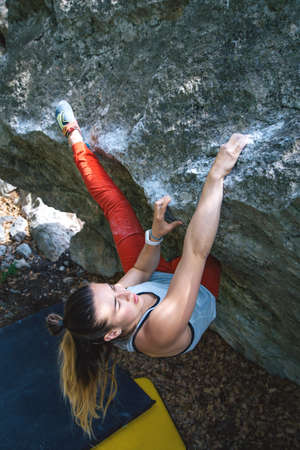 Beautiful young athletic girl climbing hard boulder problem in forest. Sport climbing, bouldering. Outdoor.