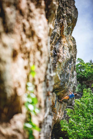 Athletic man climbs a rock in the forest with rope. Sport climbing, lead.