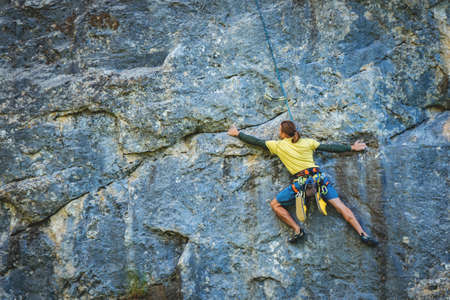 Athletic man climbs a rock in the forest with rope. Sport climbing, lead. Back view.