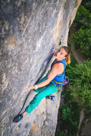 Athletic beautiful blonde hair woman climbs a rock in the forest with rope. Sport climbing, lead. Upper view.