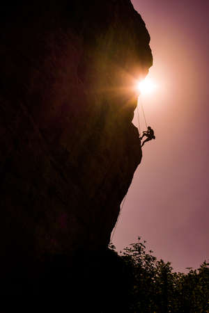 Silhouette of athletic man climbs a rock against sun with rope. Sport climbing, lead. Side view.