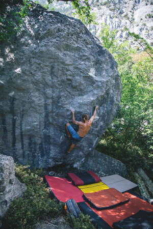 Athletic man climbing hard boulder problem in forest using special crash pads. Sport climbing, bouldering. Outdoor. Imagens