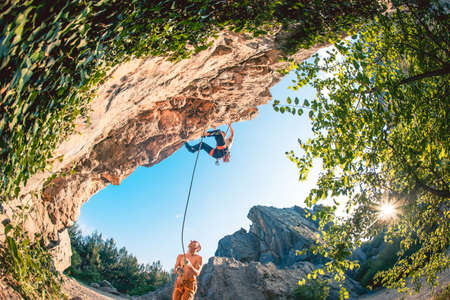 Athletic man climbs a rock, 7c category route in the forest with rope, against sunset and the other one belay him. Sport climbing in Crimea, lead. Wide viewing angle.
