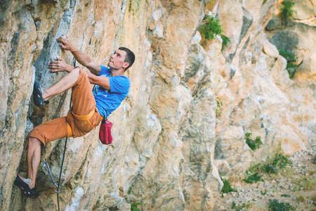 Athletic man climbs a rock in the forest with rope. Sport climbing in Crimea, lead.