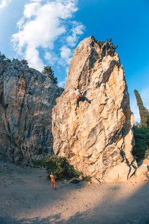 Athletic man climbs a rock, 7c category route in the forest with rope, against sunset and the other one belay him. Sport climbing in Crimea, lead. Wide viewing angle. 免版税图像