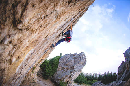 Athletic man climbs a rock, 7c category extreme overhanging route in the forest with rope. Sport climbing in Crimea, lead. Imagens