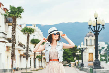 Beautiful dark hair woman walking down the street along shops and palms, smiles and touches her straw hat.