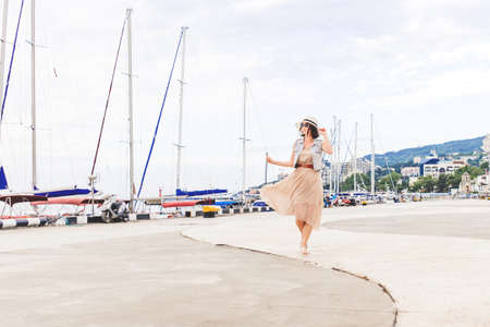 Beautiful dark hair woman walking down sea port and yachts, smiles and touches her straw hat.