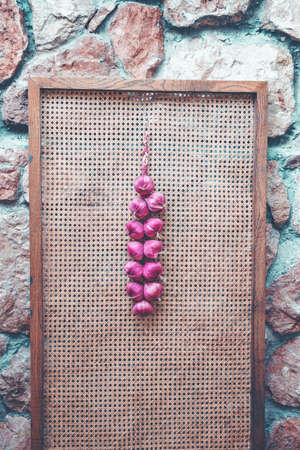 Vivid colorful violet bunch of onion hanging on wooden background. Part of cafe interior.