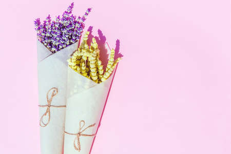 Flat lay style composition of lemongrass and lavender herbs  flower wrapped into craft paper on colorful  background. Imagens