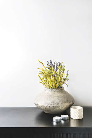 Interior design of room, mock-up, vase and lavender and lemon grass herbs bouquet, candles, white books on black table and white wall. Minimalism style. Imagens