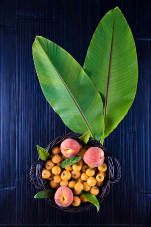 Colorful composition of tropical fruits, orange, peaches, medlar on black bamboo background. Flat lay style.