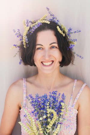 Portrait of beautiful smiling dark hair woman with lemon grass and lavander herbs in her hair. Natural beauty consept. Stock Photo