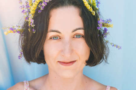 Portrait of beautiful smiling dark hair woman with lemon grass and lavander herbs in her hair. Natural beauty consept. Imagens