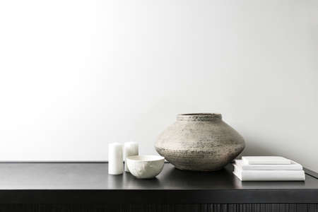 Interior design of room, mock-up, vase, candles, white books on black table and white wall. Minimalism style.