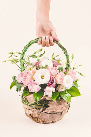 Hand holding beautiful roses flower bouquet packed in basket on beige background.