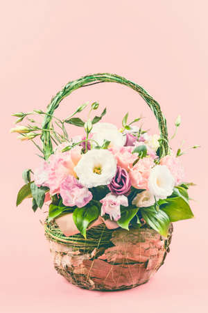 Beautiful roses flower bouquet packed in basket on pink background. Imagens