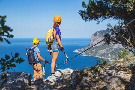 Man and woman standing at the edge of a rock stop climbing via ferrata and looking at the sea landscape.