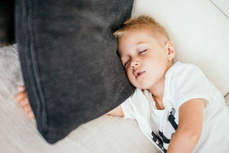 Cute blonde hair kid of 4 years old sleeping on a sofa. Day rest.
