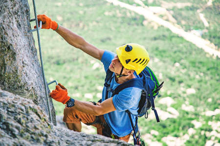 Man in helmet and special equipment climbing mountain via ferrata by sunny day in Crimea.