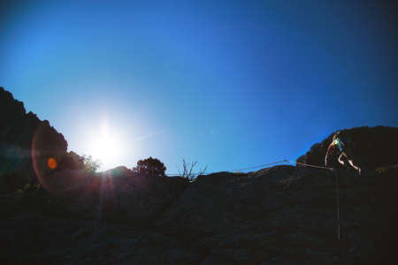 Silhouette of man in helmet and special equipment climbing mountain via ferrata by sunny day in Crimea.