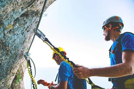 Man belays partner in mountain via ferrata using safety device. Crimea. Imagens