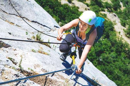 Woman in helmet and special equipment climbing high mountain via ferrata. Crimea.