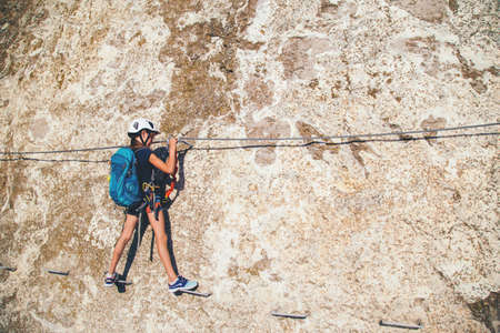 Kindermädchen von 10 Jahren in Helm und spezieller Sicherheitsausrüstung, die Hochgebirgsklettersteige klettert. Krim.