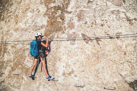 Niño niña de 10 años en casco y equipo especial de seguridad escalando alta montaña vía ferrata. Crimea.