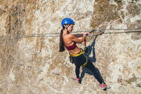 Mujer en casco y equipo especial de escalada de alta montaña vía ferrata. Crimea.