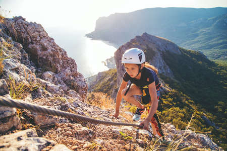 Kid girl of 10 years old in helmet and special safety device equipment climbing high mountain via ferrata. Crimea. Imagens