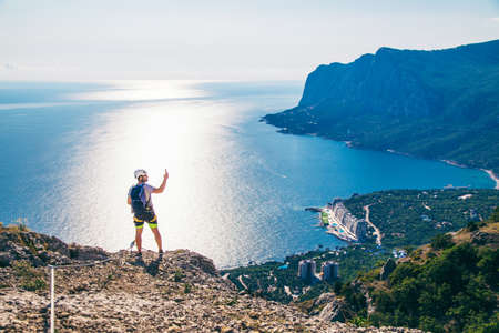 Man in helmet and special equipment make photo at the top of mountain by sunny day in Crimea.